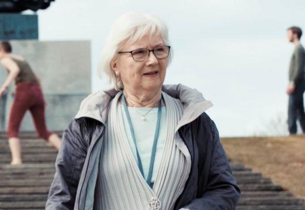 En eldre kvinne på gåtur i Vigelandsparken. Rundt halsen bærer hun en trygghetsalarm, fra Stendi.