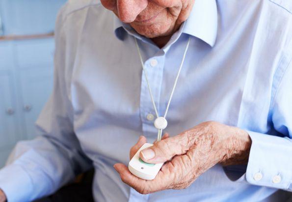 En eldre mann i lyseblå skjorte sitter og holder i en trygghetsalarm som han har hengende rundt halsen.
