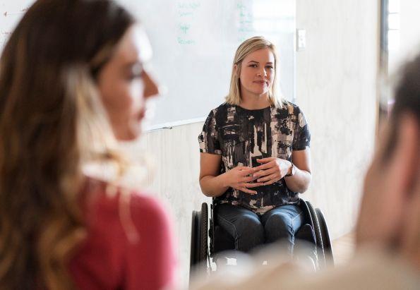 Lærer i rullestol lytter til elevenes diskusjoner