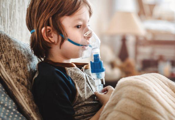 En ung gutt sitter i sofaen med en pustemaske over nese og munn.