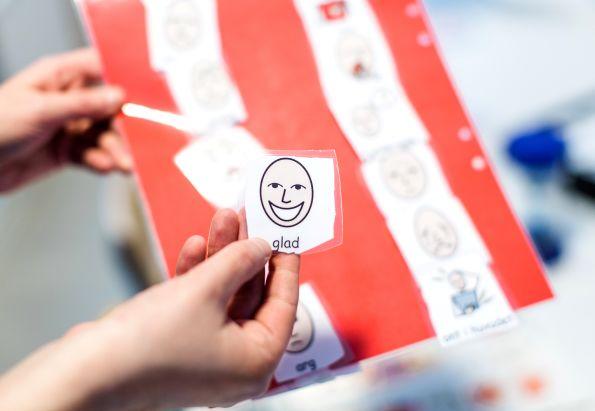 Brikker med forskjellige følelser på et rødt brett, for å gi mennesker med demens mestring.