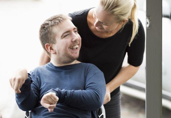Ung mann i rullestol sammen med en Stendi assistent.
