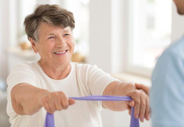 En eldre kvinne holder i et treningsstrikk. Holder seg aktiv med trening på Gabels Park.