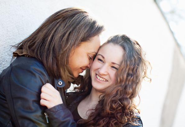 En fostermor og en fosterdatter klemmer og smiler