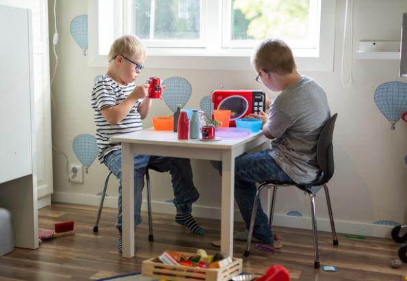 To små gutter med downs syndrom sitter og leker seg i et av Stendis boenheter for utviklingshemmede.
