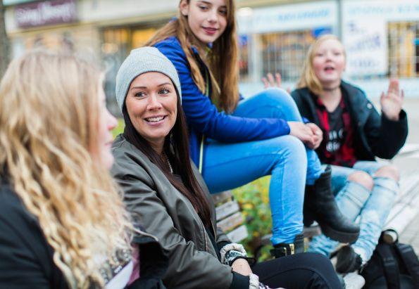 En fostermor med tre tenåringsjenter sitter på en benk og prater.