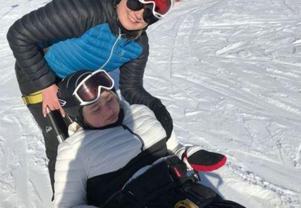 Jente med funksjonsnedsettelse koser seg i skibakken, sammen med sin personlige assistent fra Stendi BPA