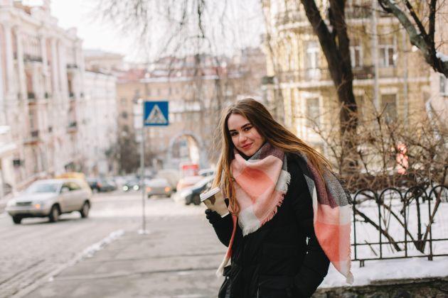 Ung kvinne med kaffekopp i hånden, med bybildet i bakgrunn.