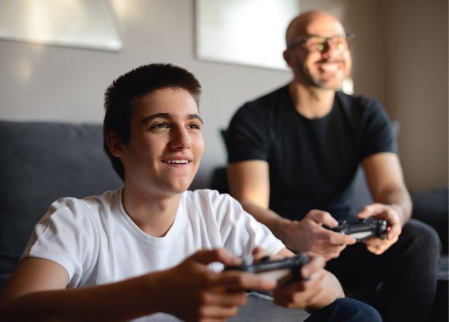 Mann og gutt spiller Playstation sammen