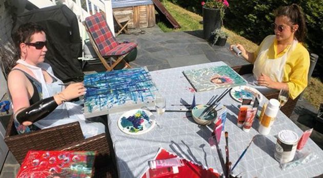 Kvinne med proteser på begge armene sitter ved en bord og maler med assistenten sin fra Stendi.