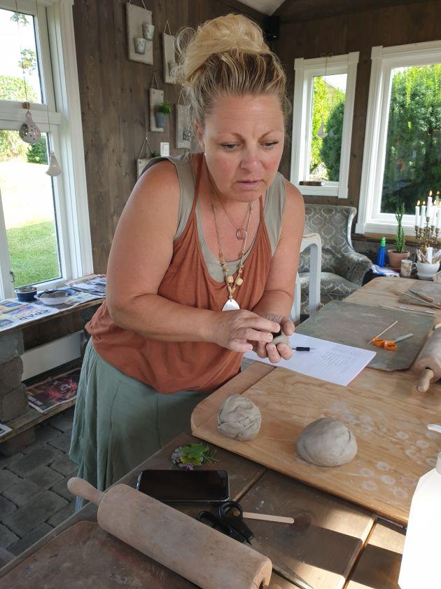 Kunstner og keramikkinstruktør Alexandra Visnes former leire i hendene.