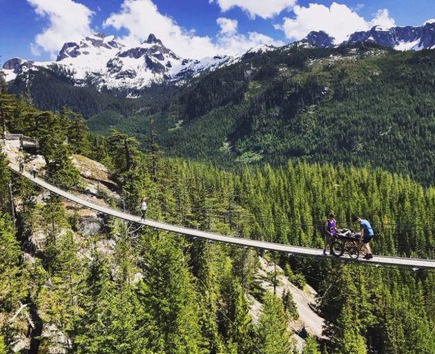 Torstein Lerhol, som ligger i rullestol får hjelp over en hengebru i vakker Norsk natur.