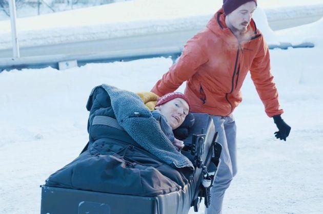 Assistent fra Stendi hjelper en mann som ligger i en rullestol, ute i snøen.