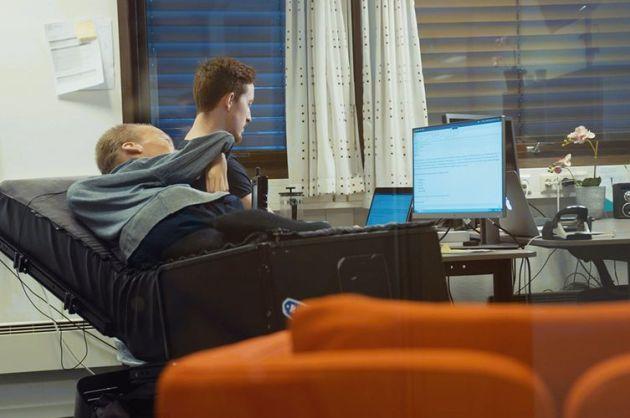 Torstein ligger i en rullestol, ved siden av sitter hans assistent fra stendi og skriver på daten.