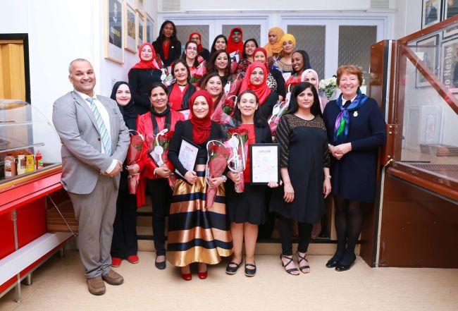 En gruppe bydelsmødre står sammen og holder diplomer og blomsterbuketter. Sammen med dem er BU-leder i Stovner Rashid Nawaz, organisasjonsleder Nasreen Begum, og ordfører i Oslo Marianne Borgen.