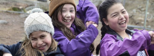 Tre jenter er sammen og ler.