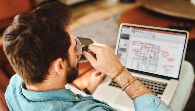 Mann ser på computer og drikker kaffe