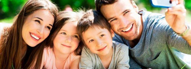 Familie med to barn smiler mot kamera