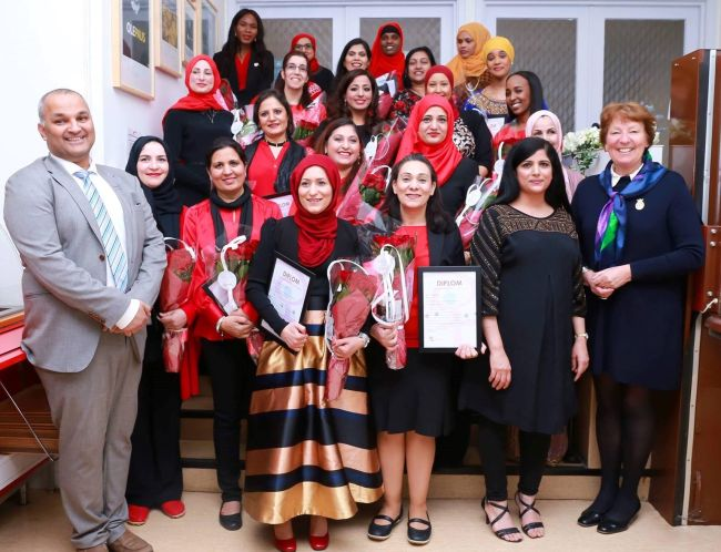 Bydelsmødrene i bydel Stovner står oppstilt sammen på festen for deres diplomutdeling. Alle er kledt i rødt og svart. Bydelsmor Fatima står fremst.