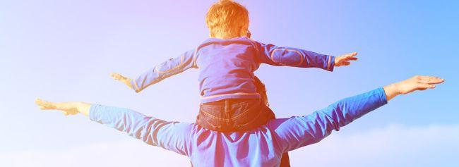 En gutt sitter på skuldrene til en voksen