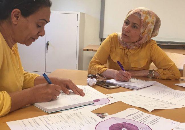 Fatima sitter sammen med bydelsmor Hayat ved et bord og prater. Foran dem ligger mange papirer og skjemaer de fyller ut.
