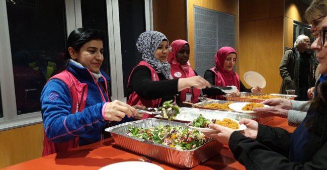 Fire bydelsmødre står sammen bak et bord med store gryter med mat, og serverer folk. De er alle kledd i rosa bydelsmor-vester.