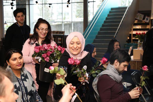 To bydelsmødre står og deler ut rosa roser til folk på kvinnedagsmarkeringen i 2019. De smiler.