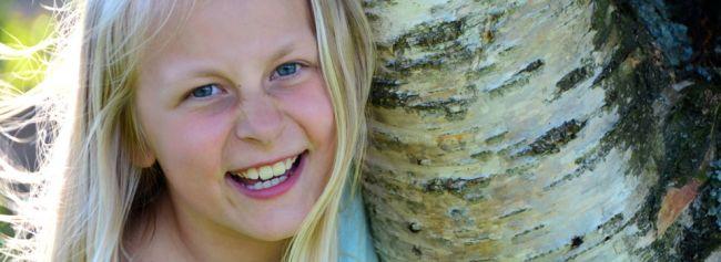 Jente smiler og holder rundt et tre