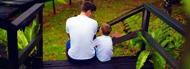 Far og sønn sitter på trappa og prater