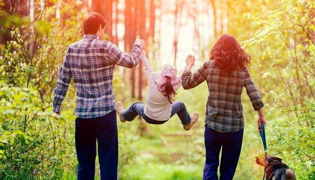 Holder hender og foreldre som løfter opp datteren mellom seg