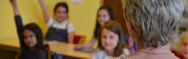 Jente rekker opp hånda i klassen