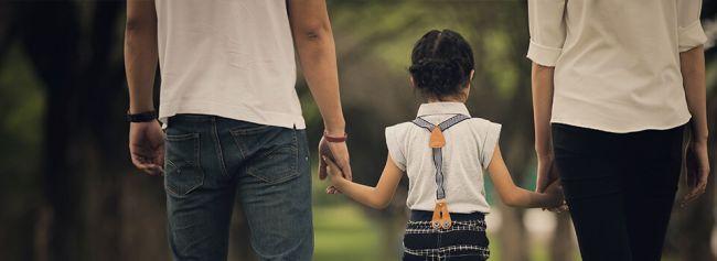 Jente holder hånden til mor og far