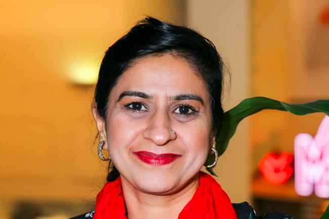 Portrettbilde av bydelsmor Mahreen, som er kledd i rødt.