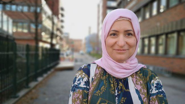 Portrettbilde av bydelsmor Fatima som står utenfor et murbygg på Tøyen og smiler til kamera.
