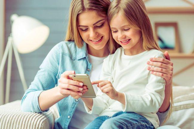 mor og datter ser på mobil
