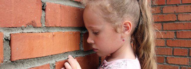 Jente ser mot murveggen