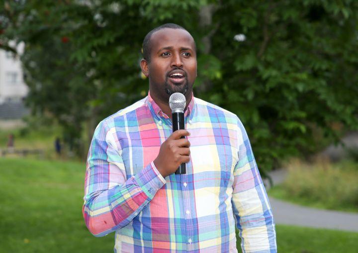 En man står og snakker i en mikrofon utendørs. Bildet er tatt i verdensparken på Furuset under Bydelsfedres grillfest i 2019.