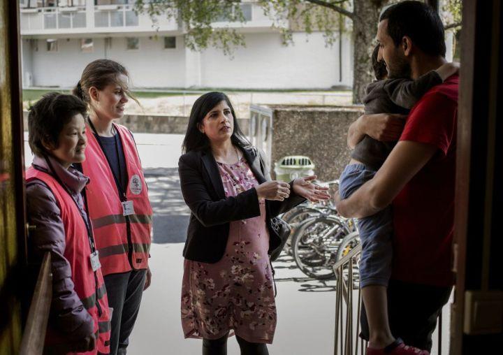 Tre bydelsmødre står utenfor en bolig og snakker med en mann med et barn på armen.