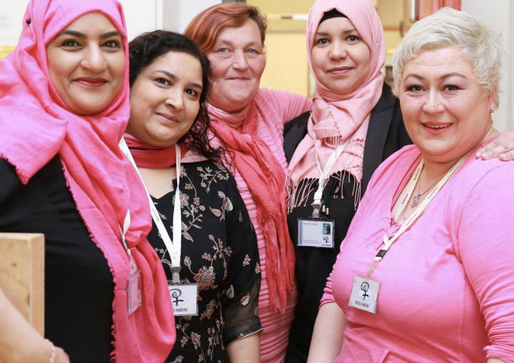 Fem bydelsmødre står side ved side med armene rundt hverandre. De er alle kledd i rosa. Bildet pryder forsiden av Bydelsmødre Norges årsrapport for 2018.