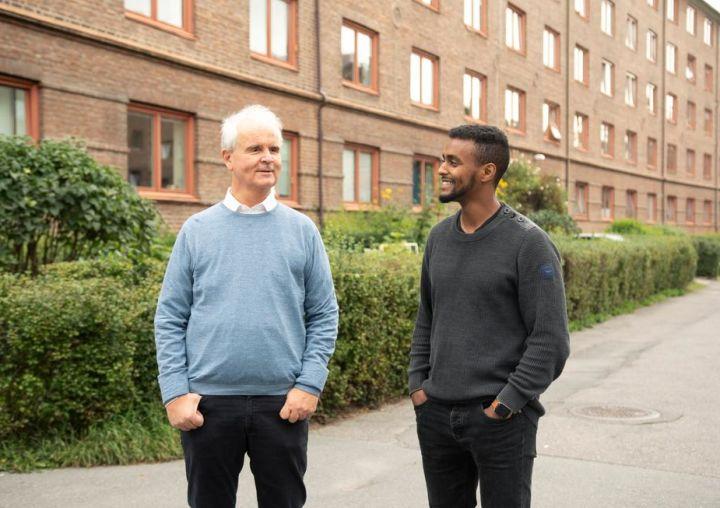 Prosjektleder Lars Semmerud og prosjektmedarbeider Thomas Haile i Bydelsfedre står sammen utenfor en blokk på Stovner