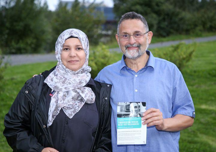 """En mann og en kvinne står sammen utendørs. Kvinnen er bydelsmor, og mannen holder en brosjyre med påteksten """"temakveld om psykisk helse hos innvandrere"""""""