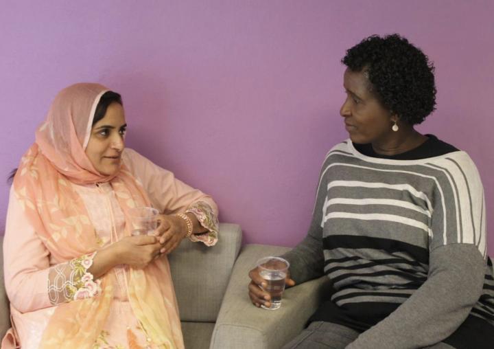 To bydelsmødre sitter sammen i en sofa og prater. Bildet bryder Bydelsmødre Norges årsrapport for 2017.