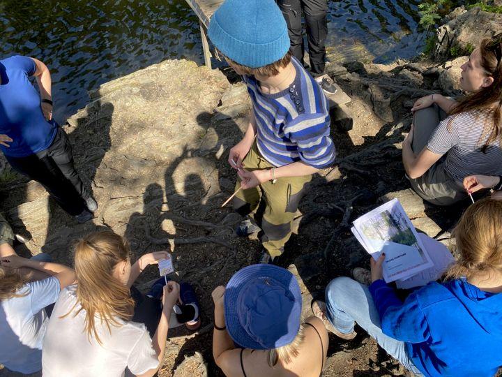 Elever på feltdag i naturfag ved et vann i marka