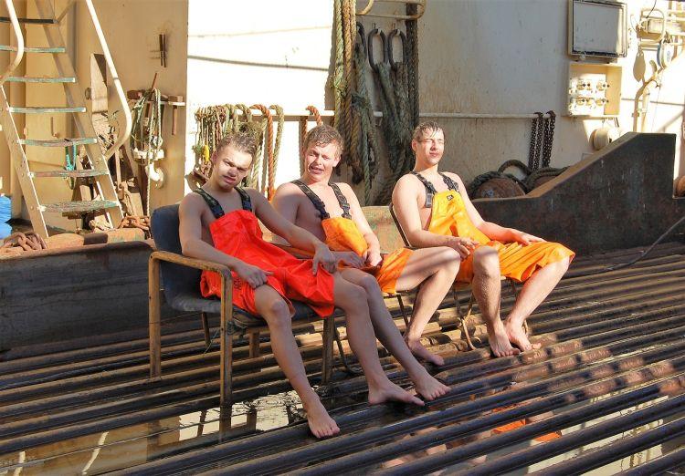 tre smilende gutter i orange regnbukse slapper av på fiskebåt