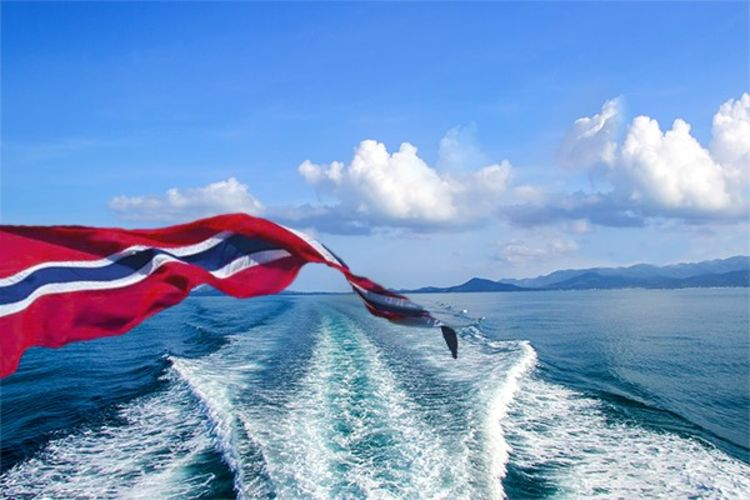 vaiende norsk vimpel på båt med sjø i bakgrunnen