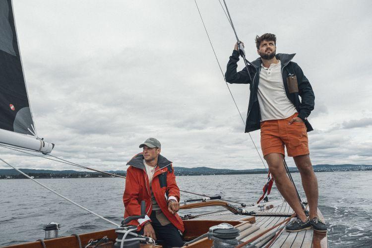 Drifter Jacket fra Amundsen Sports til herre i fargen offwhite. Bildet viser rød og blå jakke på menn ombord på seilbåt