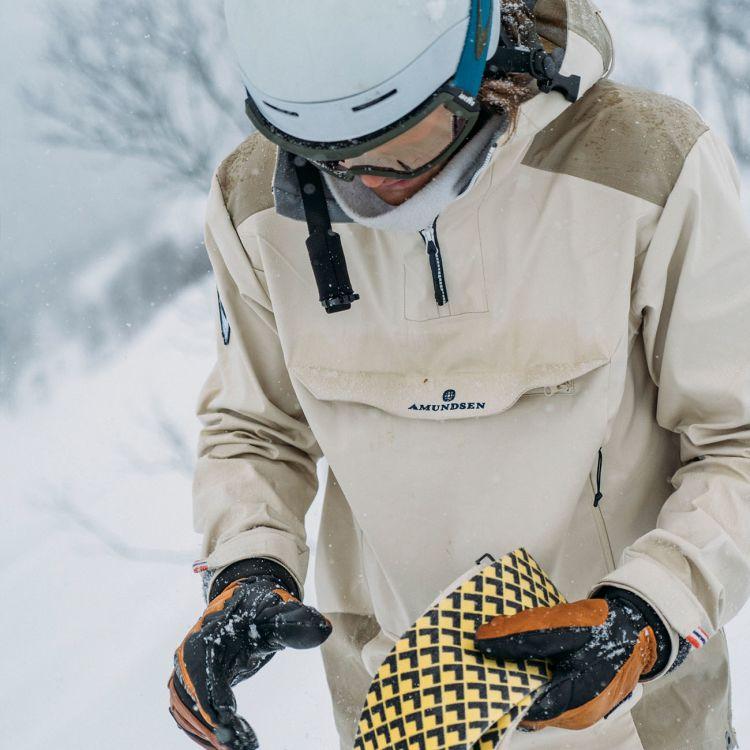 Skauen anorak fra Amundsen Sports til herre i fargen warm sand. Jakken er avbildet på modell ute og prepper ski i snøen
