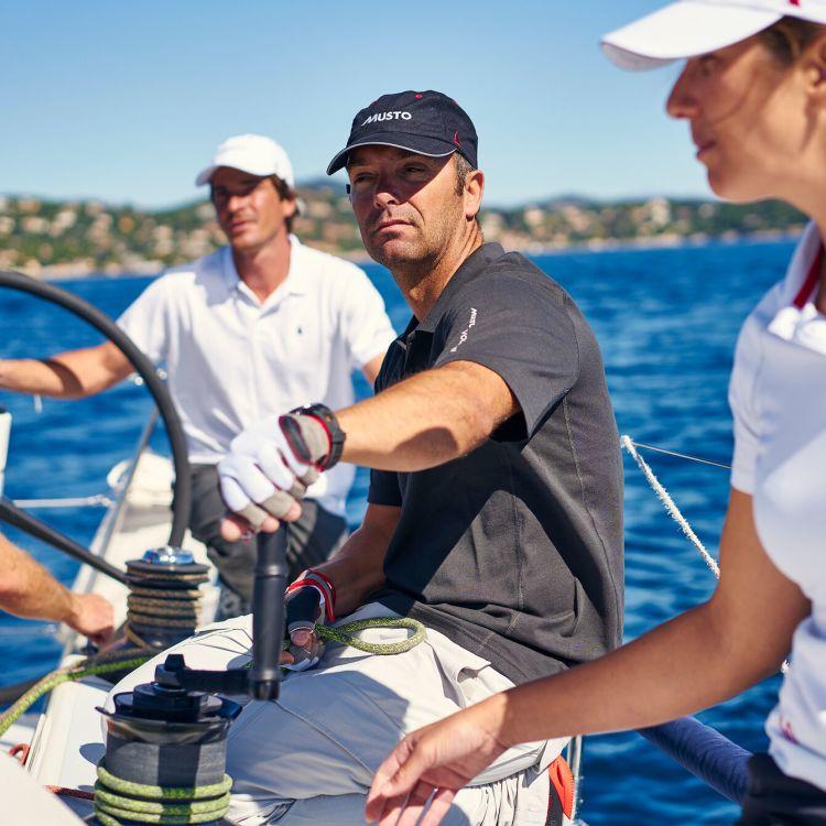 Essential Fast Drying Caps fra Musto i fargen navy. Bildet viser caps på seilere ombord på båt