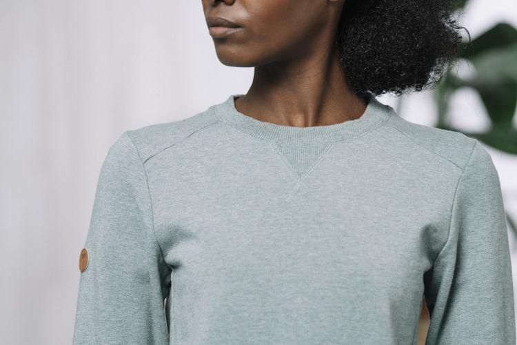 Womens Lunde Sweater i fargen Beryl Green Melange. Bildet viser nærbilde av genseren på damemodell i studio