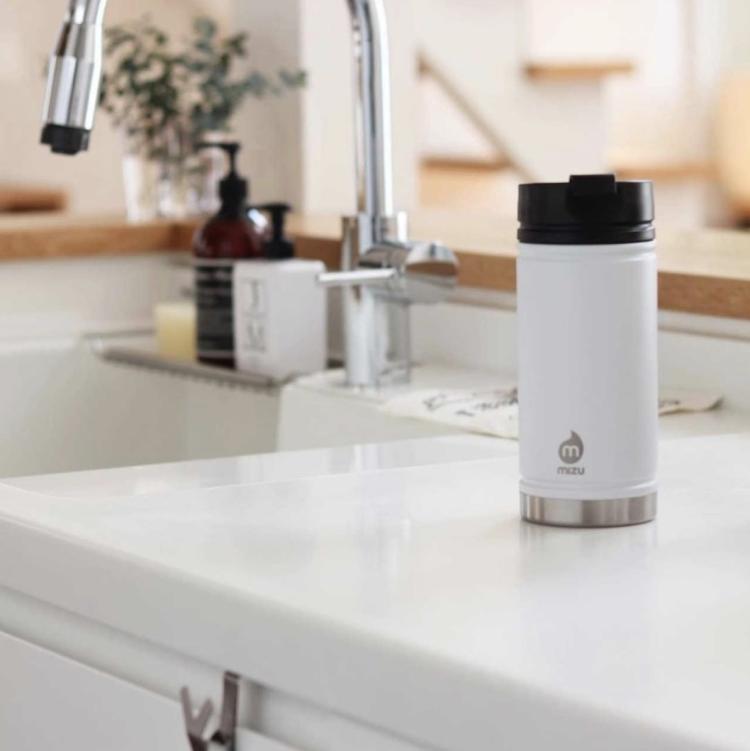 V5 Kaffekopp fra Mizu i fargen white. Bildet viser koppen stående på kjøkkenbenken